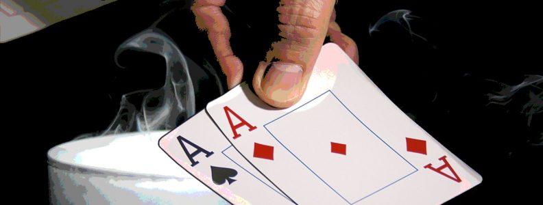 Closeup dari Pegangan Tangan Memegang Pasangan Ace Di Atas Lilin yang Hancur