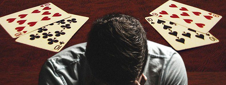 Pria Dengan Wajah di Tangan Dengan Latar Belakang Meja Poker